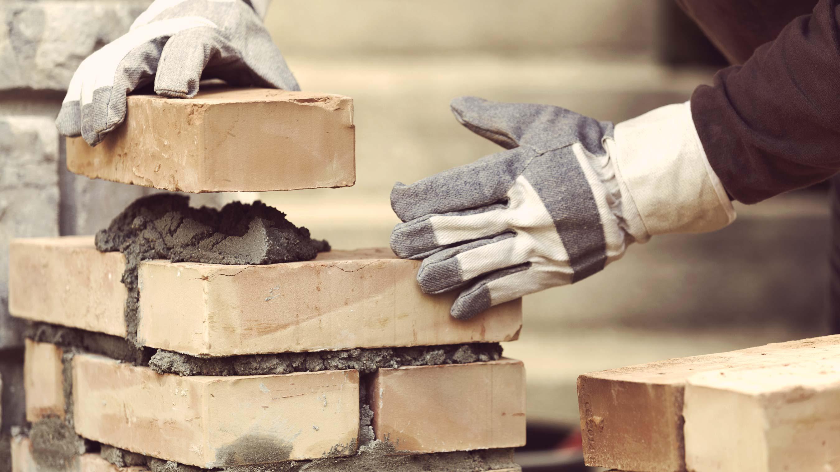 maçon effectuant pose de briques
